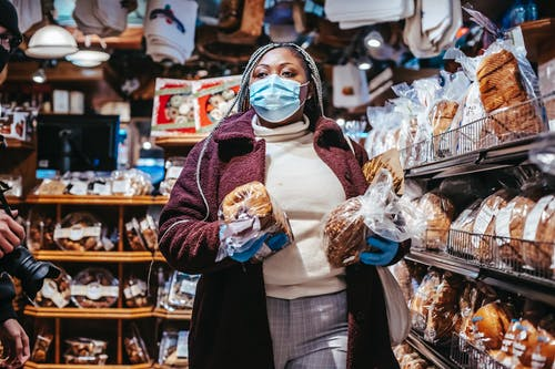 African American female buyer in protective mask and gloves carrying loafs of bread in grocery store