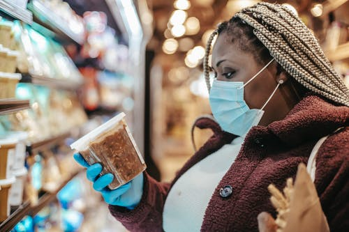 Black woman checking ingredients and manufacturing date of product