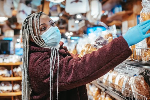 Side view of African American female buyer wearing medical mask and latex gloves choosing bread from shelf in supermarket
