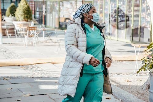 Black woman in medical uniform walking on street