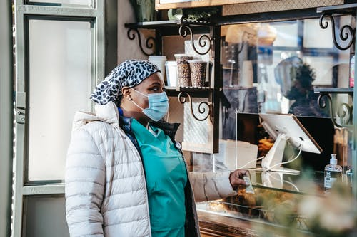 African American female medical worker in mask and uniform buying takeaway drink in coffee house