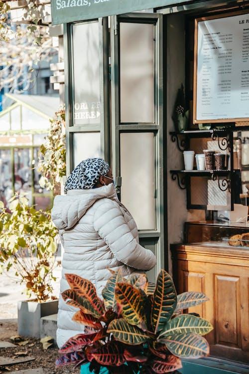 Black woman choosing hot drink in coffee house