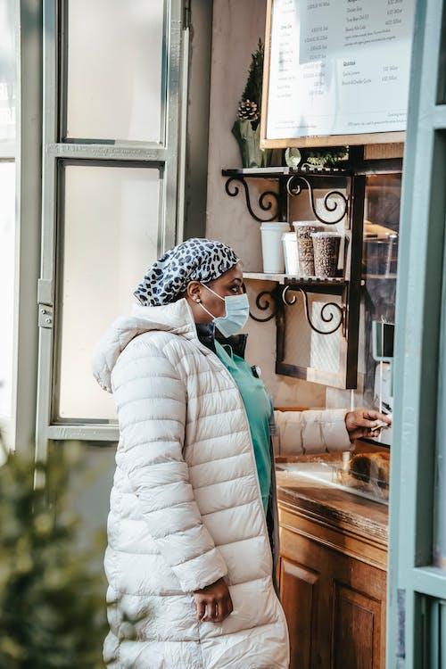 Black nurse in medical mask buying coffee