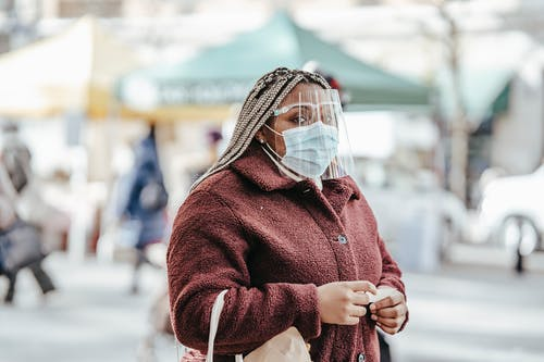 Faceless adult African American lady in warm clothes and protective mask standing in city street with bag and piece of paper in hands in daylight