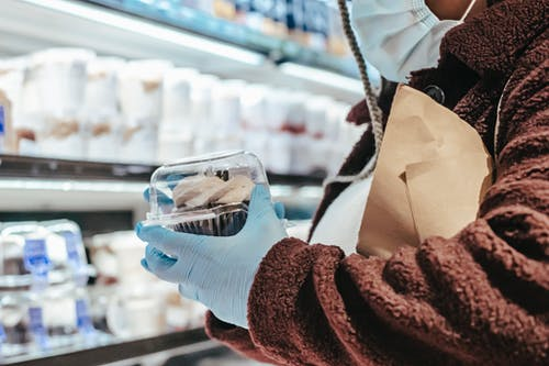 Anonymous black female in mask and gloves shopping in supermarket