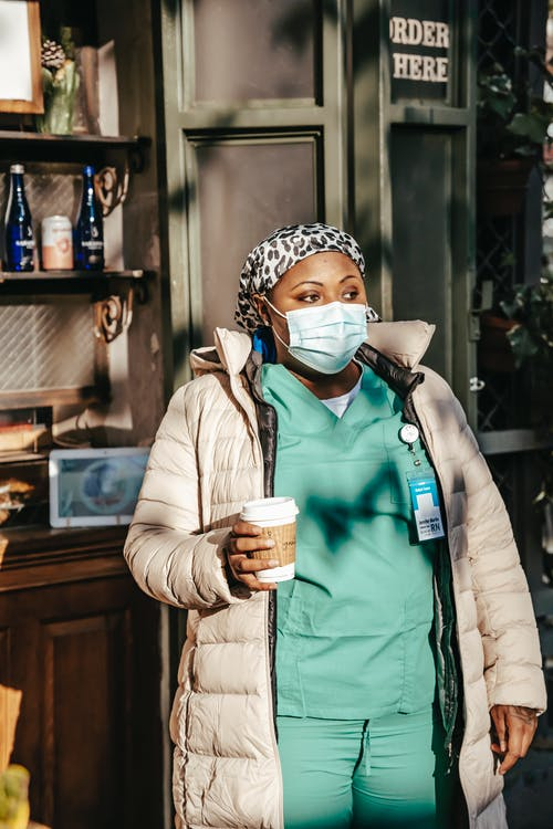 Black nurse in outerwear and mask standing in modern cafeteria