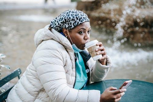 Adult black nurse enjoying takeaway coffee in outdoor cafe