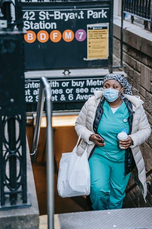Mujer En Abrigo Verde E Hijab Blanco Sentado En Un Banco De Metal Gris