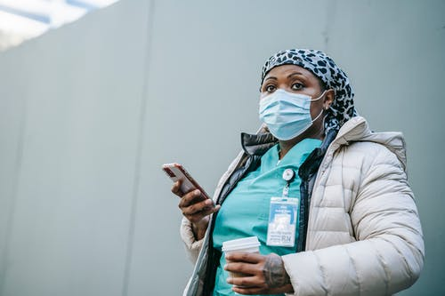 Serious adult African American nurse in warm clothes and protective face mask standing with cup of takeaway coffee and browsing mobile phone on street
