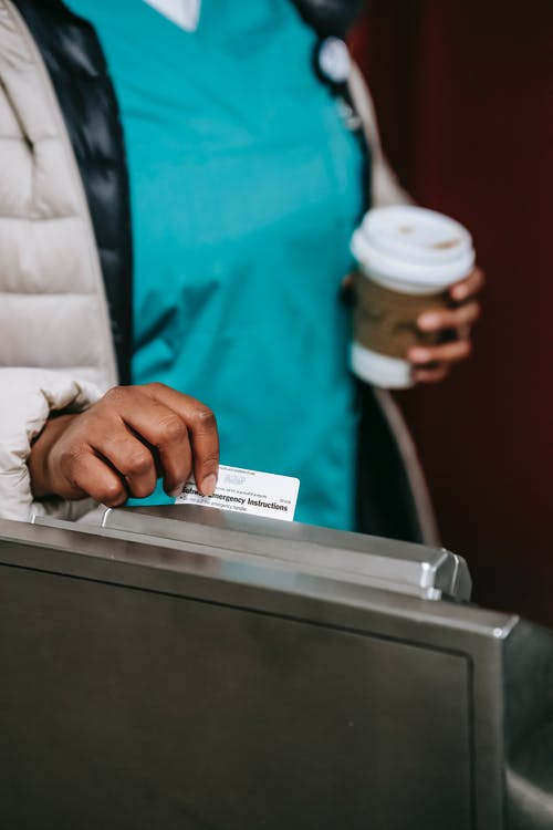 Crop faceless black nurse swiping pass card in metro turnstile