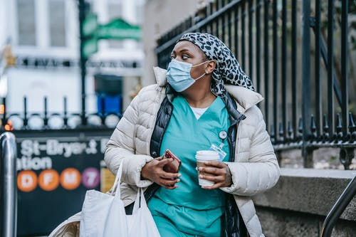 Adult black nurse with takeaway coffee leaving metro station