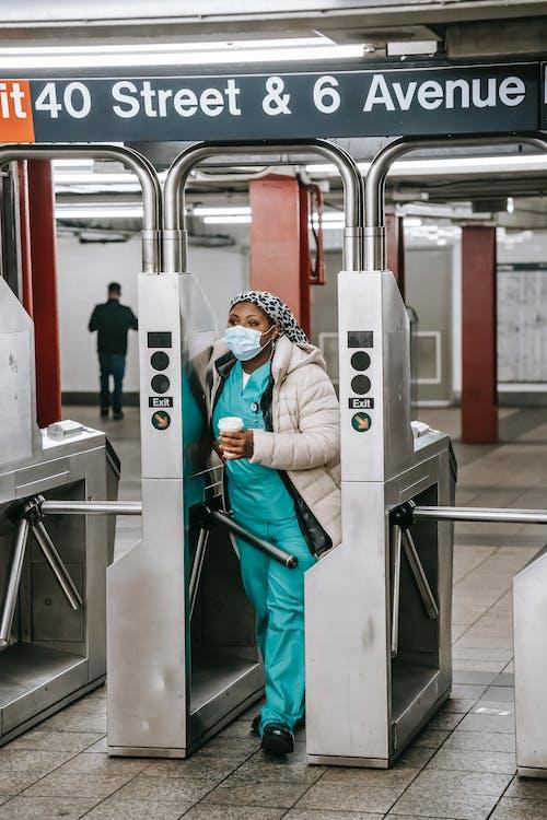 Adult black nurse passing turnstile in metro station