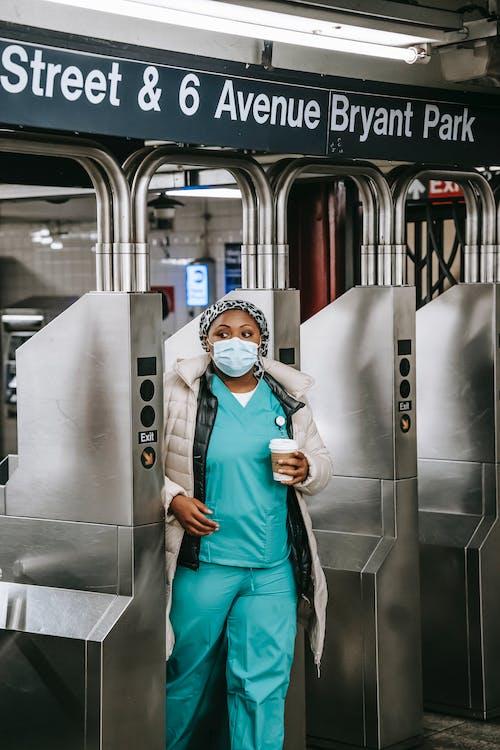 Adult black nurse passing through turnstile in metro station