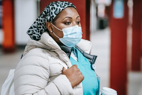 Pensive black nurse in mask standing in public place