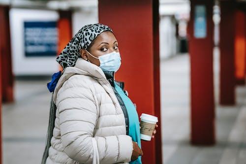 Black nurse in outerwear standing on metro platform