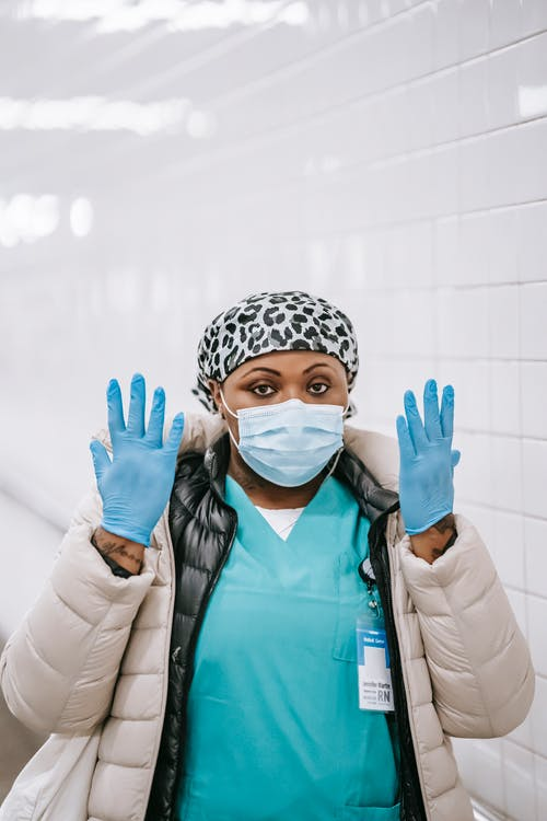 Calm adult African American nurse in uniform warm clothes and face mask raising arms and showing hands in latex gloves while standing in public place and looking at camera