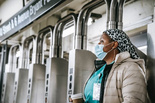 Side view emotionless African American female doctor wearing warm clothes and protective face mask passing through turnstile gates in New York underground