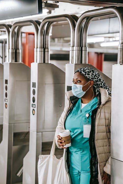 Thoughtful adult African American female doctor with takeaway coffee in blue uniform warm clothes and protective mask passing through turnstile gate while commuting to work in metro station