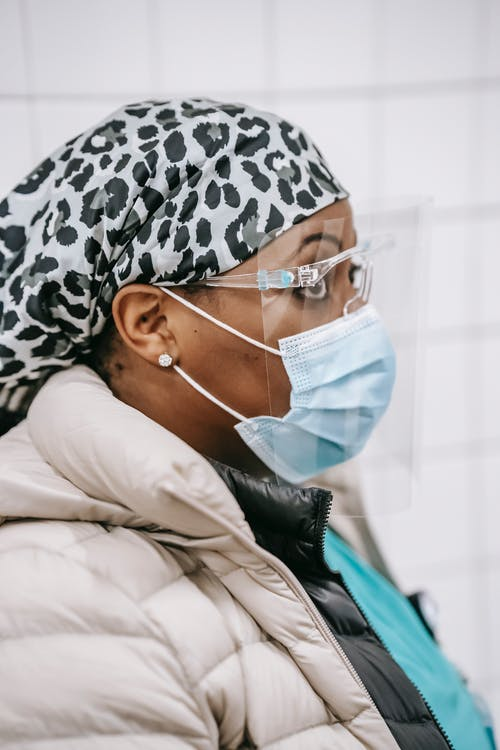 Side view of black woman in medical mask and protective glasses standing in tiled room and looking away