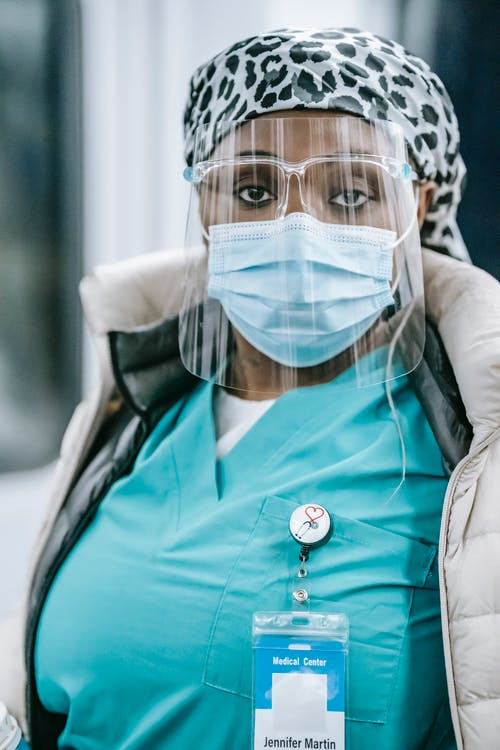 Serious African American female medic in sterile mask and glasses standing in hospital and looking at camera