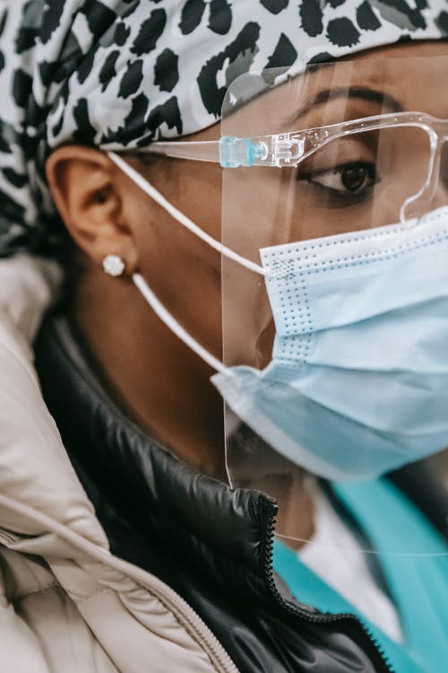 Crop black female doctor in protective mask and hat standing in hospital while looking away