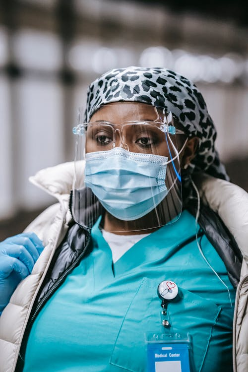 Confident African American nurse in sterile mask and uniform looking away while working in hospital