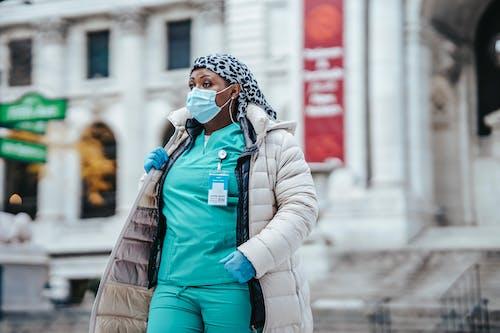 Black woman in doctor uniform crossing street