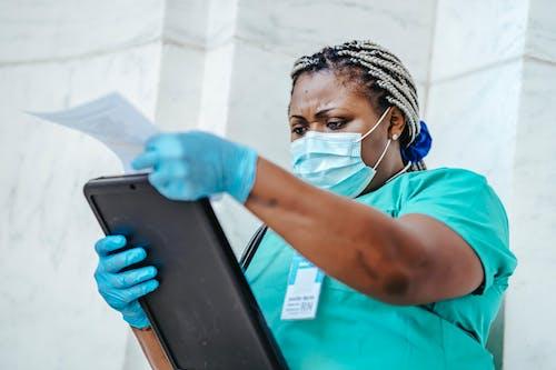 Frau Im Blauen Rundhalsausschnitt T Shirt, Das Weiße Maske Hält, Die Schwarzen Tablet Computer Hält