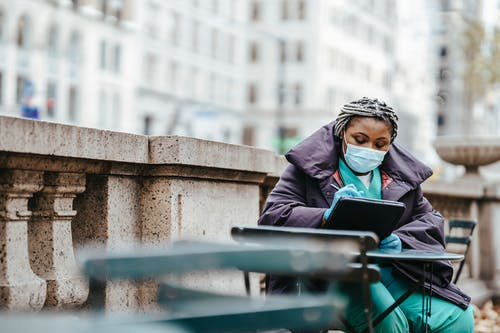 Focused African American woman in protective mask and gloves sitting at table and writing information in balcony