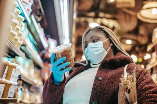 Black woman in protective mask buying products