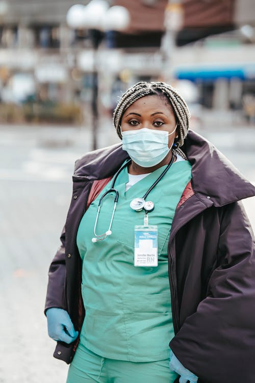 Black doctor in mask standing on city street