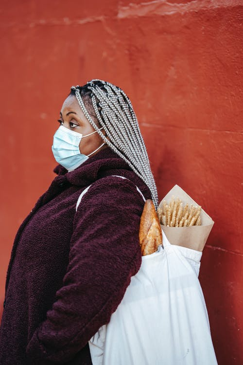 Serious African American woman in protective mask standing with shopper with purchases against red wall and looking away