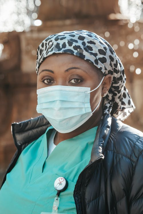Pensive African American woman doctor in sterile mask and uniform looking at camera against blurred background in sunny day