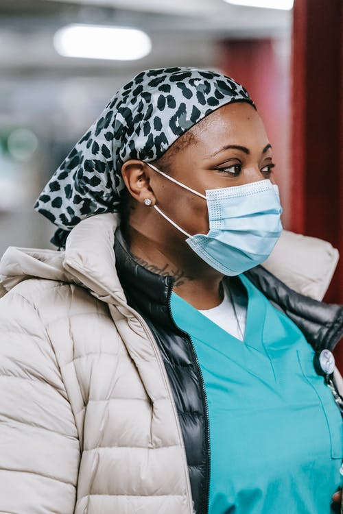 Serious black female doctor in protective mask and uniform looking away against blurred light corridor