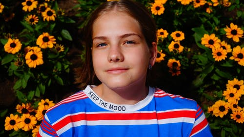 Crop glad preteen girl in casual shirt standing against lush bush with yellow fragrant flowers in garden and looking at camera