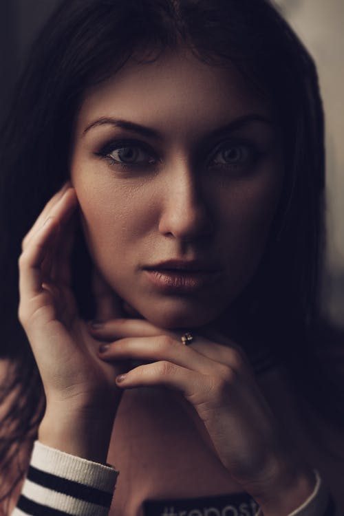 Crop young sensitive brunette in casual wear touching pretty face tenderly and looking at camera