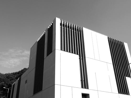 From below black and white rack exterior of modern house with unusual design located on street in city against cloudy sky
