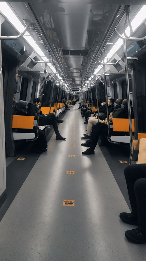 People Sitting on Black and Yellow Train Seats