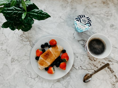 Top view composition of delicious homemade croissant with fresh blueberries and strawberries placed near coffee yogurt and green plant