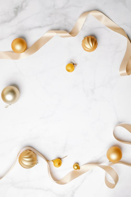 Top view of composition of decorative golden baubles and golden ribbon placed in white marble surface