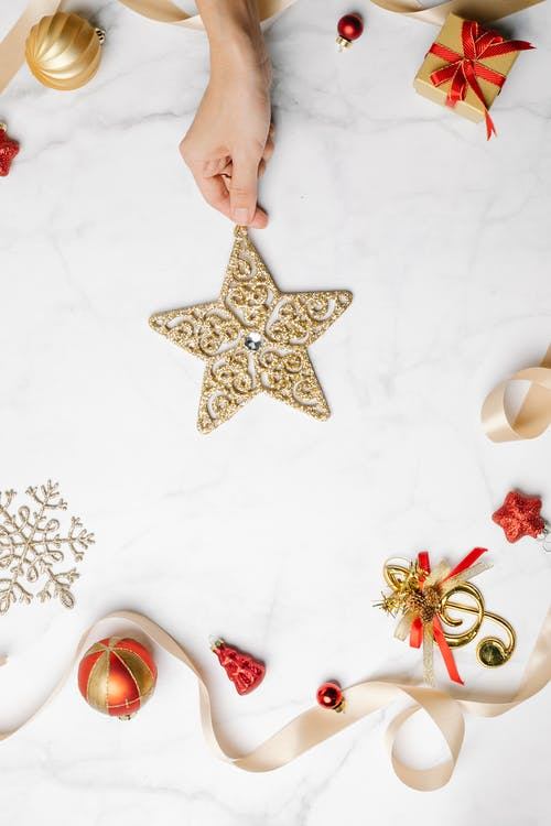 Person showing festive sparkling decorative star among Christmas decorations