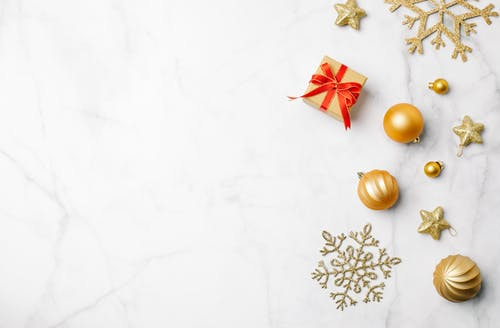 Top view of golden festive baubles with stars and snowflakes placed near small box with gift
