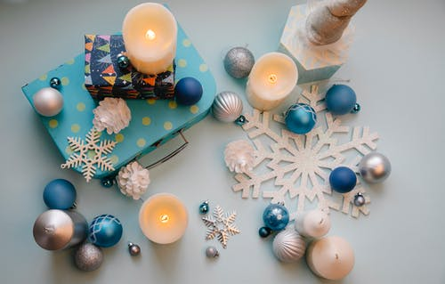 From above of assorted baubles and decorative snowflakes with flaming wax candles during New Year holiday
