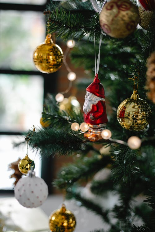 Decorated Christmas tree with baubles and Santa Claus statuette