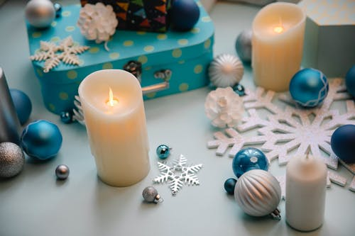 High angle of Christmas decor with metal box and flaming candles near snowflakes with baubles