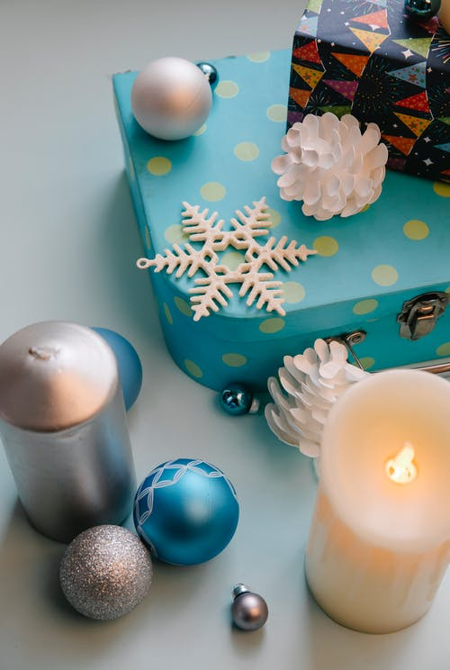 From above of glowing wax candle near decorative balls and snowflake during New Year holiday on gray background