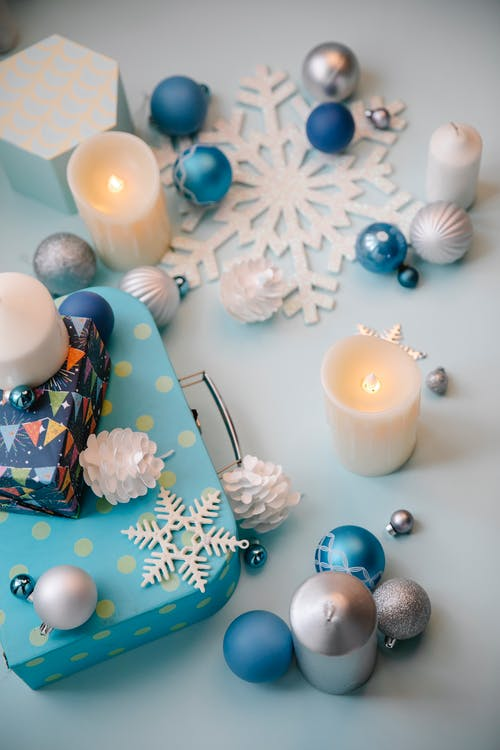 Assorted Christmas decoration with flaming candles on gray background