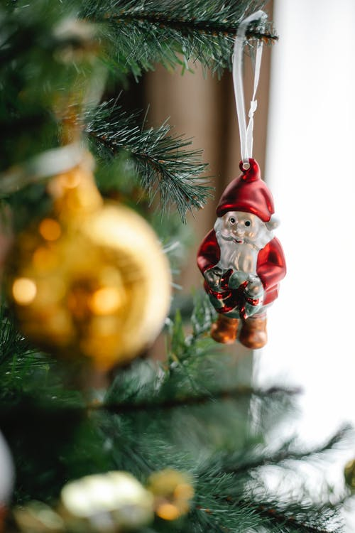 Decorative Saint Nicholas hanging on fir tree with shiny bauble during New Year holiday in house