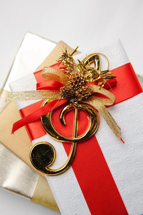 Top view of golden treble clef on present boxes with ribbons and pine cones during New Year holiday