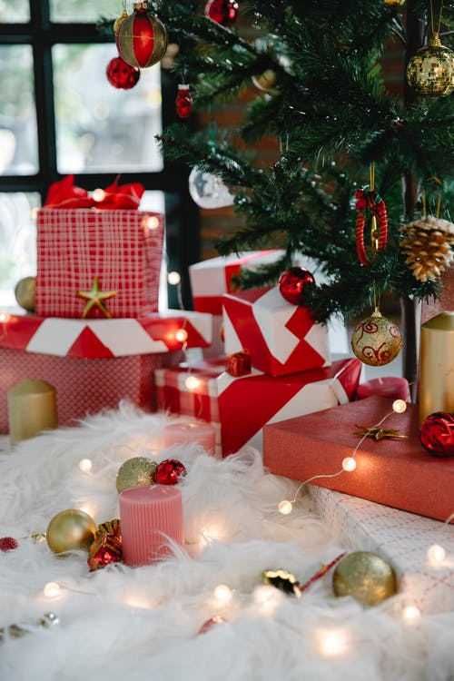 Caixas De Presente Vermelhas E Brancas Ao Lado Da árvore De Natal Verde Com Enfeites